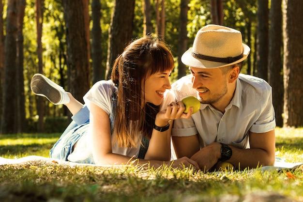 Jong mooi paar dat op een deken in het park ligt. familie picknick. Premium Foto