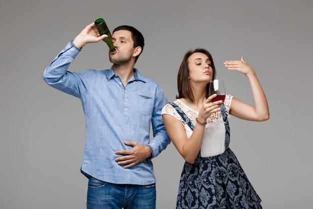 Jong mooi paar het drinken van wijn en bier over grijze muur Gratis Foto