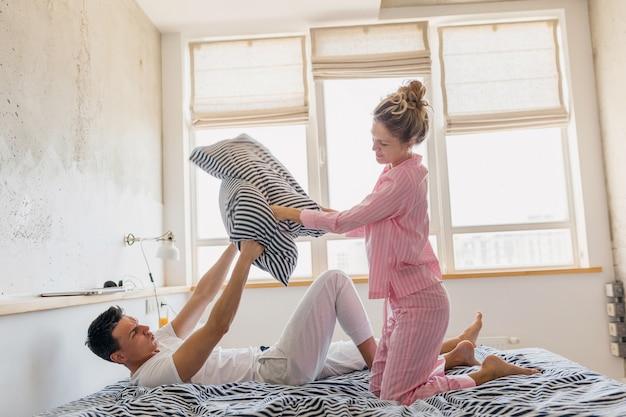 Jong mooi paar met plezier op bed in de ochtend blijven samen alleen thuis Gratis Foto