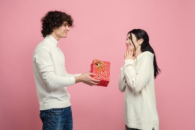 Jong, mooi paar verliefd op roze studiomuur Gratis Foto