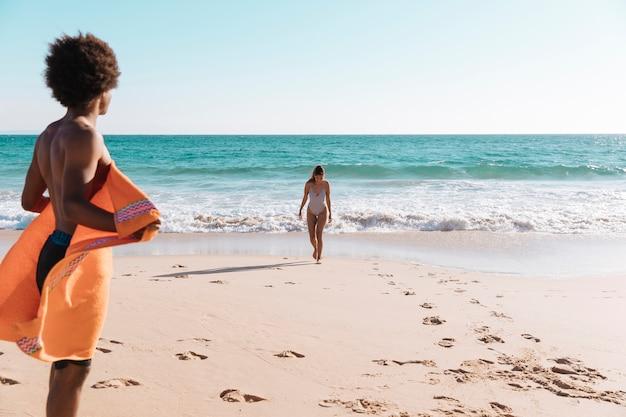 Jong multi-etnische paar ontspannen op het strand Gratis Foto