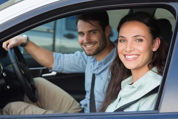Jong paar dat bij de camera glimlacht Premium Foto