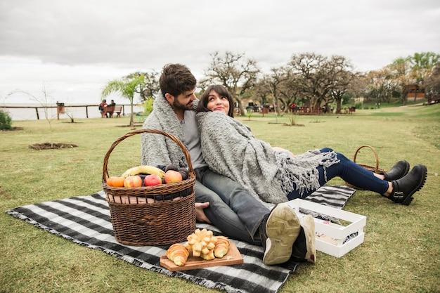 Jong paar dat bij picknick in het park geniet van Gratis Foto