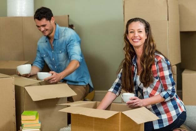 Jong paar dat elkaar bijstaat terwijl uitpakt kartondozen in nieuw huis Premium Foto