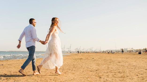 Jong paar dat elkaars hand houdt die op zandig strand loopt Gratis Foto