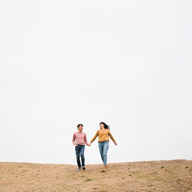 Jong paar dat holdingshanden loopt Gratis Foto