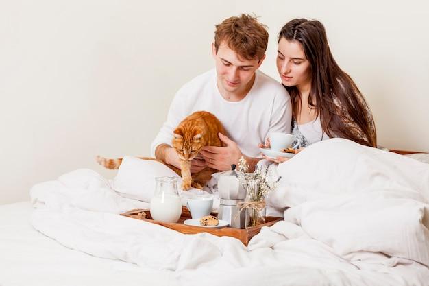 Jong paar dat ontbijt in bed heeft Gratis Foto