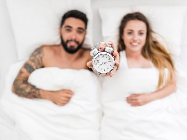 Jong paar dat op bed ligt dat wekker toont Gratis Foto