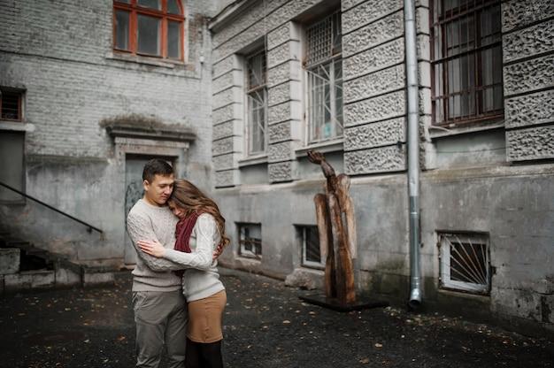 Jong paar dat op gebonden warme sweaters draagt die in liefde bij oude werf met boog en kolommen bij stad koesteren. Premium Foto