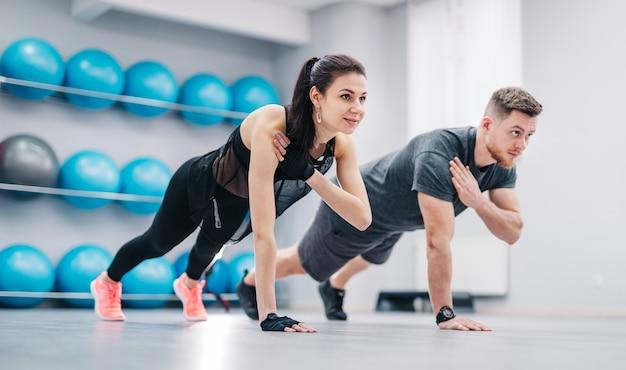 Jong paar dat opdrukoefeningen van vloer één hand samen doet Premium Foto