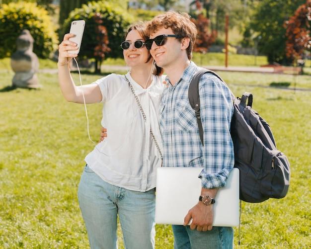 Jong paar dat selfie in het park neemt Gratis Foto