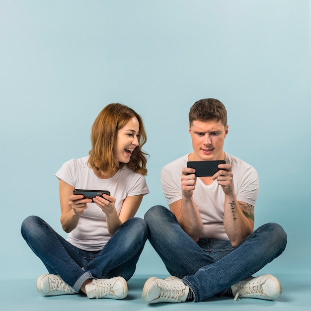 Jong paar dat van het videospelletje op cellphone geniet tegen blauwe achtergrond Gratis Foto