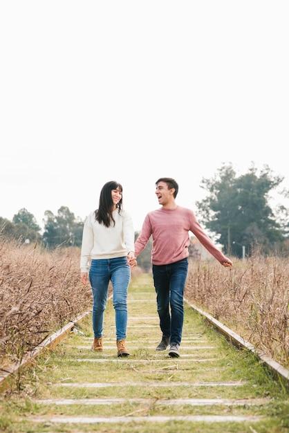 Jong paar dat van wandeling langs sporen geniet Gratis Foto