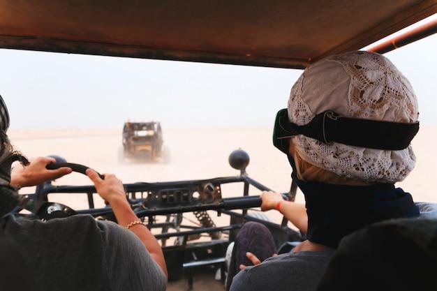 Jong paar die auto met fouten in woestijn berijden Premium Foto