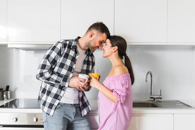 Jong paar die elkaar bekijken die kop van koffie en sapglas houden in keuken Gratis Foto