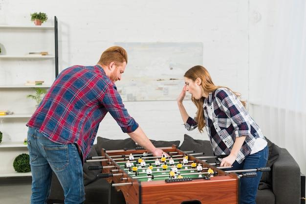 Jong paar die het de voetbalspel van de voetballijst in de woonkamer spelen Gratis Foto
