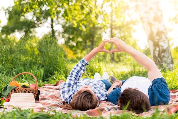 Jong paar die op plaid rusten en hartgebaar tonen Gratis Foto