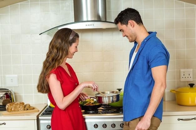 Jong paar die voedsel samen in keuken thuis voorbereiden Premium Foto