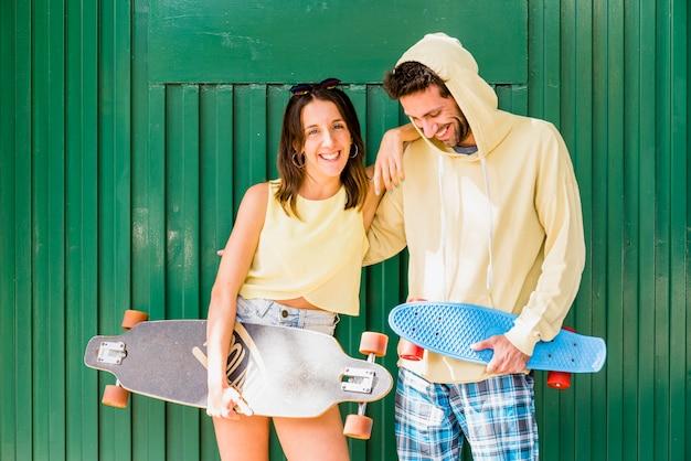 Jong paar hipsters knuffelen met skateboards Gratis Foto