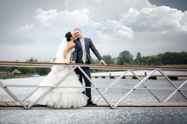 Jong paar in liefde de bruid en bruidegom met boeket het stellen op een pijler, huwelijksdag in de zomer. genieten van een moment van geluk en liefde. Premium Foto