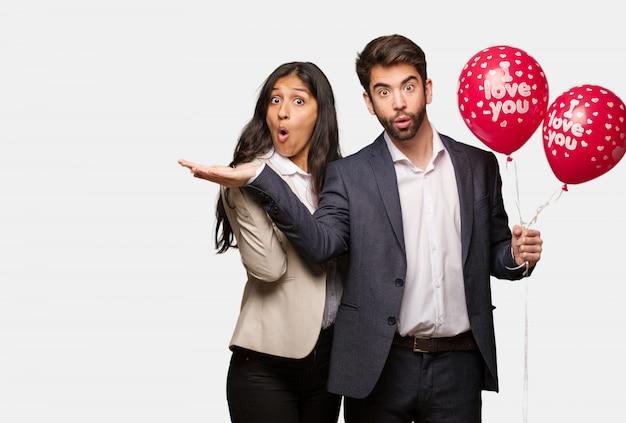 Jong paar in valentijnsdag die iets op palmhand houden Premium Foto