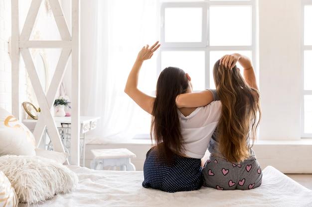 Jong paar knuffelen en zittend op het bed Gratis Foto