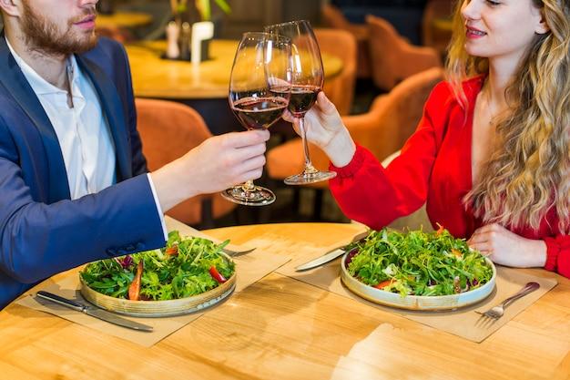 Jong paar rinkelende glazen aan tafel Gratis Foto