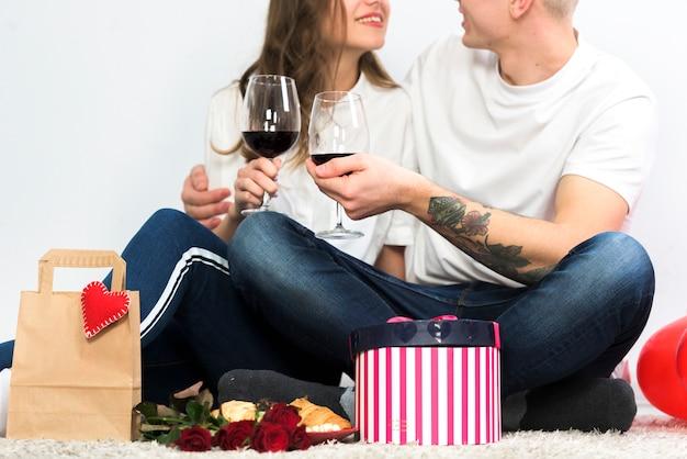 Jong paar rinkelende glazen wijn op de vloer Gratis Foto