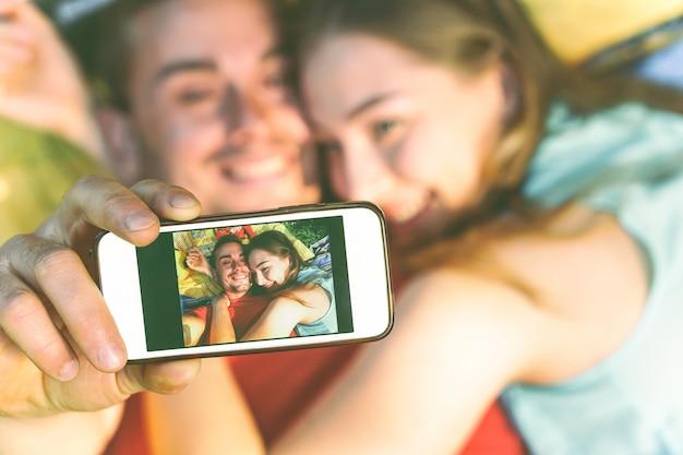Jong paar van minnaars nemen die op gras liggen die een selfie met mobiele telefoon nemen Premium Foto