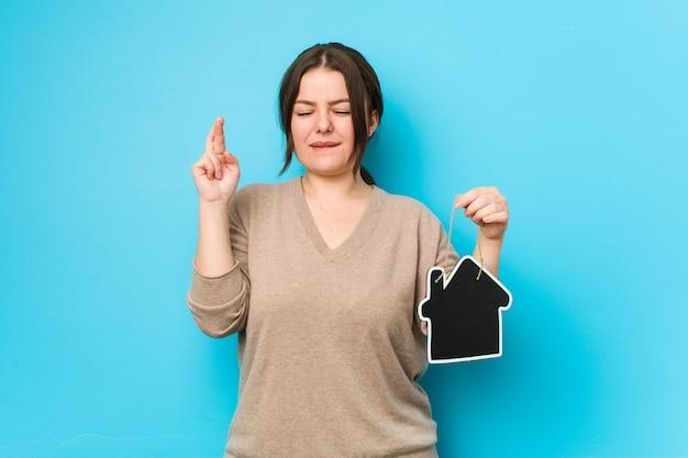 Jong plus grootte curvy vrouw die een huispictogram houden die vingers kruisen voor het hebben van geluk Premium Foto