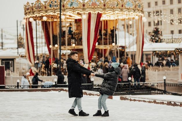 Jong romantisch koppel heeft plezier buiten in de winter voor kerstmis Premium Foto