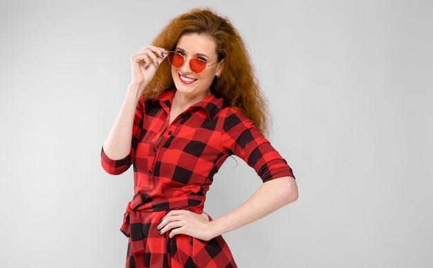 Jong roodharig meisje in een rood geruit hemd. jong meisje in een rode bril. Premium Foto