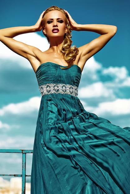 Jong sexy blond vrouwenmodel in avondjurk het stellen op blauwe hemelachtergrond Gratis Foto
