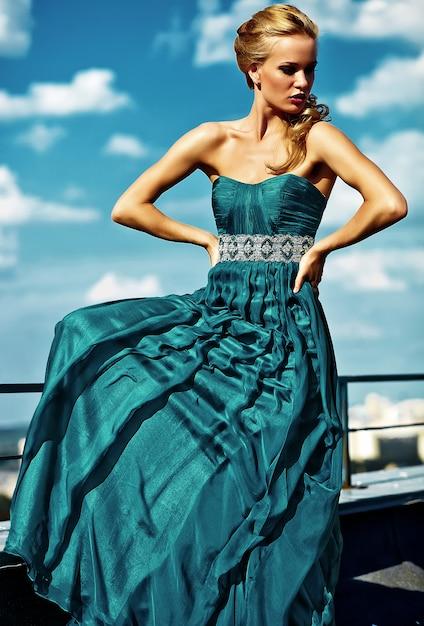 Jong sexy blond vrouwenmodel in avondjurk het stellen op blauwe hemelmuur Gratis Foto