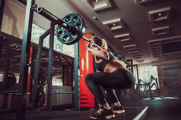 Jong sexy meisje in de gymnastiek die hurkzit doet Premium Foto