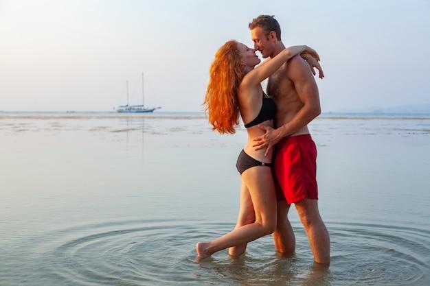 Jong sexy romantisch paar verliefd gelukkig op zomer strand samen plezier dragen van zwemkleding Gratis Foto