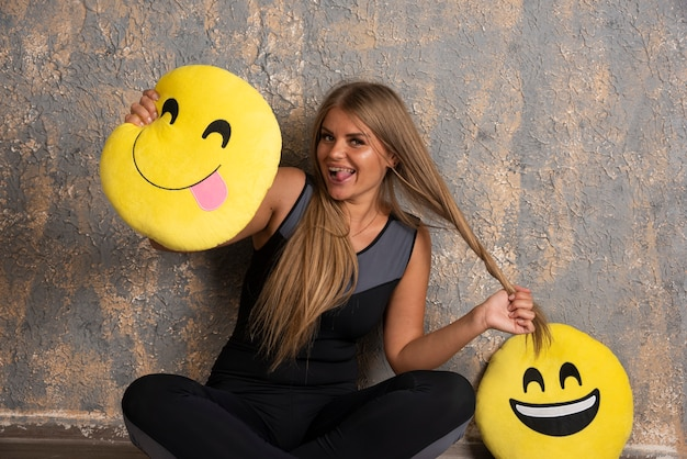 Jong sportief meisje in sportoutfits die het glimlachen en tong uit emoji-kussens houden en pret hebben. Gratis Foto