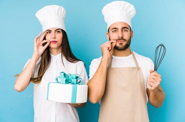Jong stel dat een cake kookt die samen met vingers op lippen wordt geïsoleerd die een geheim houden. Premium Foto