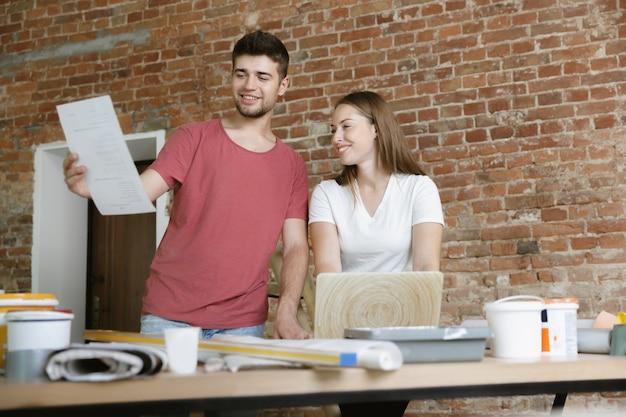 Jong stel dat zelf appartementreparatie doet. getrouwde man en vrouw die huis make-over of renovatie doen. concept van relaties, familie, liefde. bespreek het ontwerp van de muur met een notitieboekje. Gratis Foto