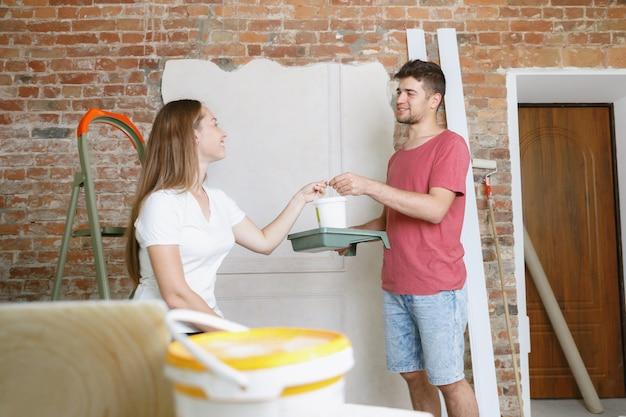 Jong stel dat zelf appartementreparatie doet. getrouwde man en vrouw die huis make-over of renovatie doen. concept van relaties, familie, liefde. samen de muur schilderen en lachen. Gratis Foto