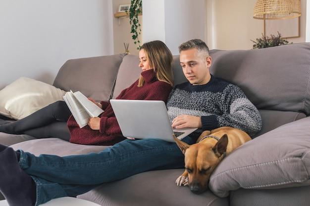 Jong stel en hun hond genieten van vrije tijd en ontspannen thuis op de bank, lezen een boek en gebruiken een laptop Premium Foto