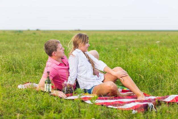 Jong stel in de zomerweide, man en vrouw die romantische picknick hebben. Premium Foto