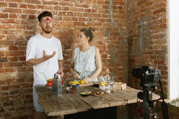 Jong stel kookt en neemt live video op voor vlog en sociale media Gratis Foto