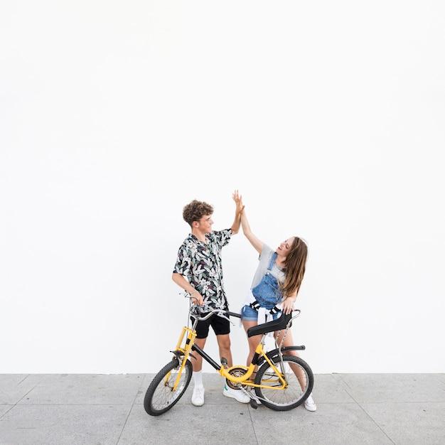 Jong stel met fiets geven high five aan elkaar Gratis Foto