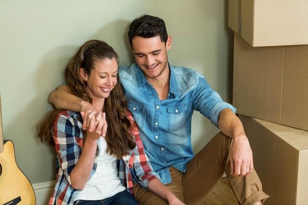 Jong stel zat samen op de vloer en lachend in hun nieuwe huis Premium Foto