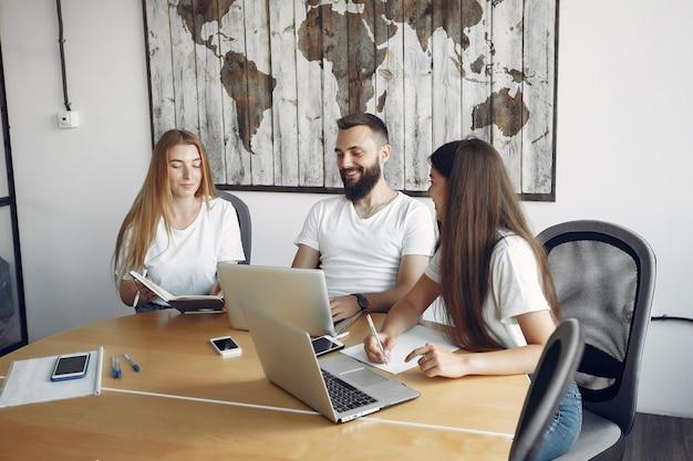 Jong team dat samenwerkt en laptop gebruikt Gratis Foto