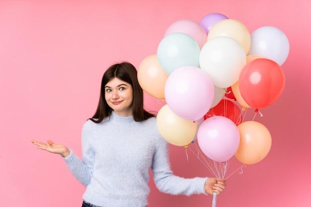 Jong tienermeisje dat veel ballons over roze muur houdt die twijfels met verwarde gezichtsuitdrukking heeft Premium Foto