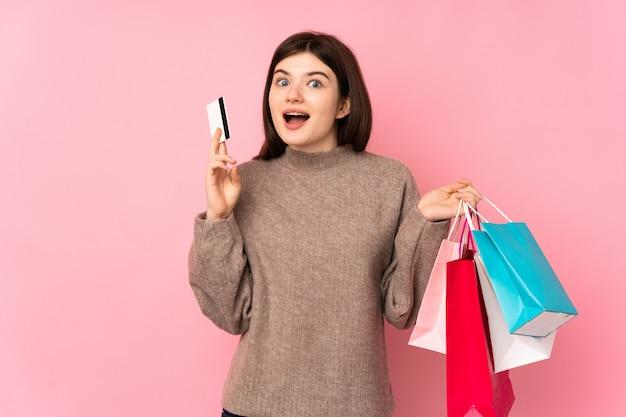 Jong tienermeisje over roze muurholding het winkelen zakken en verrast Premium Foto