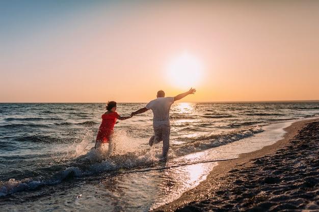 Jong verliefde paar loopt langs het strand tegen de achtergrond van de ondergaande zon Premium Foto
