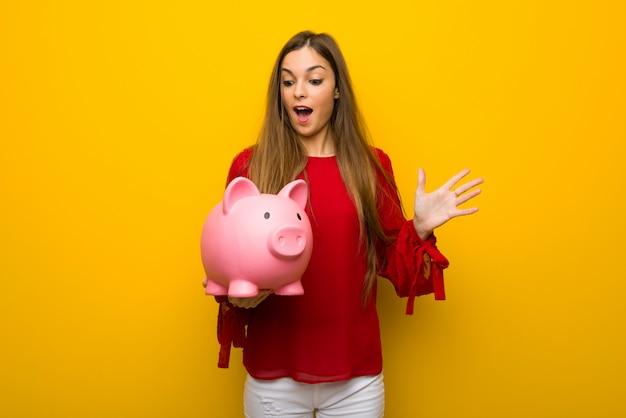 Jong verrast meisje met rode kleding over gele muur terwijl het houden van een spaarpot Premium Foto